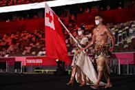 <p>Tonga's flag bearers Malia Paseka (L) and Pita Taufatofua lead the delegation during the Tokyo 2020 Olympic Games opening ceremony's parade of athletes. (Photo by HANNAH MCKAY/AFP via Getty Images)</p>
