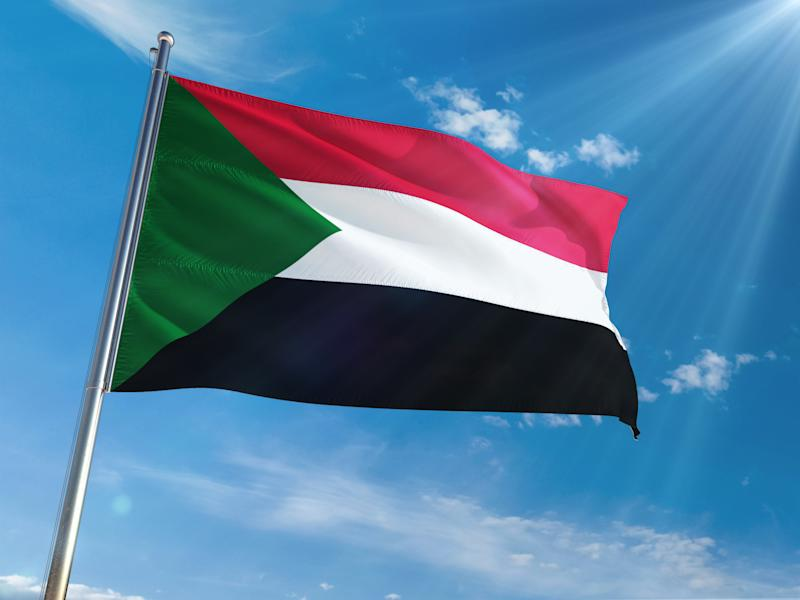 Sudan National Flag Waving on pole against sunny blue sky background. High Definition