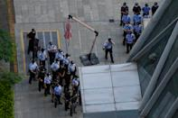 Chinese police and security personnel prepare for duty outside the Evergrande headquarters in Shenzhen, China, Friday, Sept. 24, 2021. Seeking to dispel fears of financial turmoil, some Chinese banks are disclosing what they are owed by the real estate developer that is struggling under $310 billion in debt, saying they can cope with a potential default.(AP Photo/Ng Han Guan)