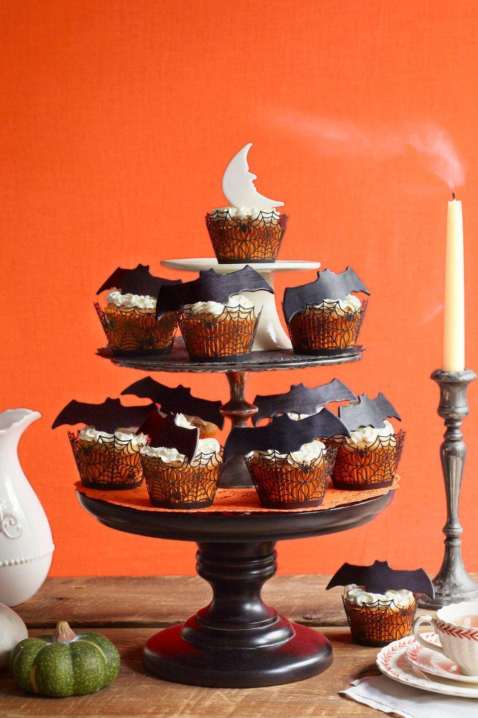 """<p>Summon this nocturnal scene by first rolling out black and white fondant separately. Use cookie cutters to create bat and moon shapes, then let fondant dry overnight to stiffen. Just before serving, perch atop buttercream-frosted cupcakes. Take cupcakes one step further with <a href=""""https://www.amazon.com/Cupcake-Wrapper-Wedding-Birthday-Decorations/dp/B01MCRDIM5?tag=syn-yahoo-20&ascsubtag=%5Bartid%7C10050.g.1366%5Bsrc%7Cyahoo-us"""" rel=""""nofollow noopener"""" target=""""_blank"""" data-ylk=""""slk:paper spider web wrappers"""" class=""""link rapid-noclick-resp"""">paper spider web wrappers</a><em>.</em></p><p><strong><a href=""""https://www.countryliving.com/food-drinks/recipes/a847/cupcakes-americana-60/"""" rel=""""nofollow noopener"""" target=""""_blank"""" data-ylk=""""slk:Get basic cupcake recipe"""" class=""""link rapid-noclick-resp"""">Get basic cupcake recipe</a>.</strong><br></p><p><a class=""""link rapid-noclick-resp"""" href=""""https://www.amazon.com/Zicome-Halloween-Cookie-Cutter-Assorted/dp/B01LYGF0PF?tag=syn-yahoo-20&ascsubtag=%5Bartid%7C10050.g.1366%5Bsrc%7Cyahoo-us"""" rel=""""nofollow noopener"""" target=""""_blank"""" data-ylk=""""slk:SHOP BAT COOKIE CUTTERS"""">SHOP BAT COOKIE CUTTERS</a></p>"""