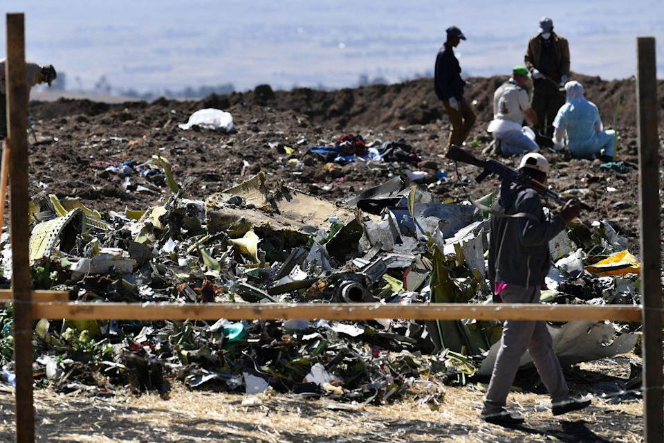 An Oromo man hired to assist forensic investigators walks by a pile of twisted airplane debris at the crash site of an Ethiopian airways operated Boeing 737 MAX aircraft on March 16, 2019 at Hama Quntushele village near Bishoftu in Oromia region. - A French investigation into the March 10 Nairobi-bound Ethiopian Airlines Boeing 737 MAX crash that killed 157 passengers and crew opened on March 15 as US aerospace giant Boeing stopped delivering the top-selling aircraft. (Photo by TONY KARUMBA / AFP)        (Photo credit should read TONY KARUMBA/AFP/Getty Images)