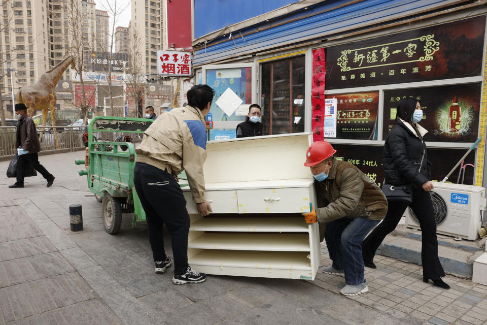 Workers move a used cabinet in Aksu in western China's Xinjiang Uyghur Autonomous Region on March 18, 2021. China is going global with its campaign to deflect criticism over its policies in the northwestern region of Xinjiang. The region's government on Wednesday, June 2, organized a transcontinental zoom call showcasing economic development and poverty elimination. (AP Photo/Ng Han Guan)