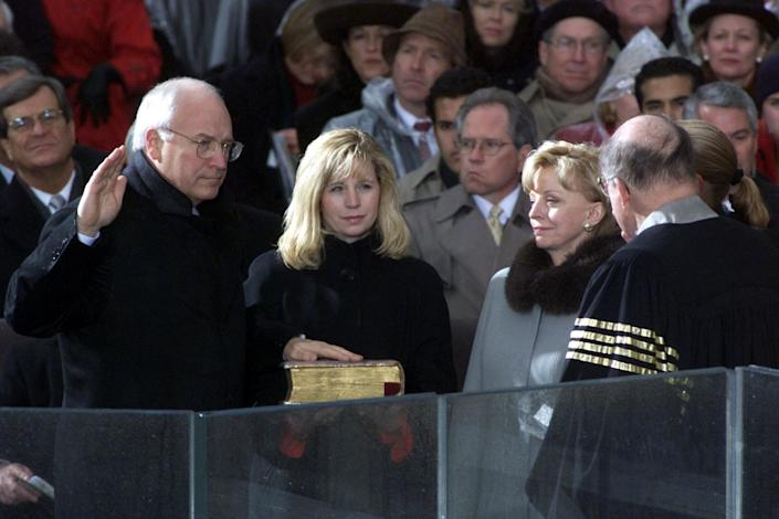 U.S. Vice President-elect Dick Cheney (L) is sworn into office by U.S. Supreme Court Justice Willaim Rehnquist (R) as his daughter Elizabeth (2nd R) holds the Bible, wife Lynne (3rd R) and daughter Mary (hidden) watch on Jan. 20, 2001 on the South Front of the U.S. Capitol. Bush was sworn in as the 43rd President of the United States. (TIMOTHY A. CLARY/AFP/Getty Images)