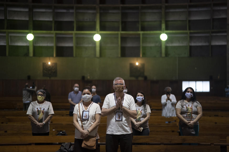 Parishioners wearing protective face masks stand during a Mass at the Metropolitan Cathedral, in Rio de Janeiro, Brazil, Saturday, July 4, 2020. Following an easing of restrictions related to COVID-19, the Catholic church in Rio celebrated its first Mass with 30% of its worshippers, while observing preventive measures to avoid spreading the new coronavirus. (AP Photo/Leo Correa)