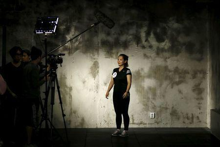 """A participant is interviewed before the start of a workout session during TV program """"The Body Show"""" at a gym in Seoul, September 19, 2015. REUTERS/Kim Hong-Ji"""