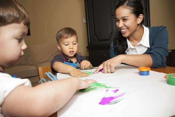 Childcare Worker Helping Two Young Boys with Fingerpaint.See more of this series: