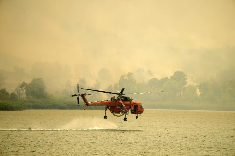 An helicopter fills water from Marathon Lake about 36 kilometres (22 miles) north of Athens, Greece, Friday, Aug. 6, 2021. Thousands of people fled wildfires burning out of control in Greece and Turkey on Friday, as a protracted heat wave turned forests into tinderboxes and flames threatened populated areas, electricity installations and historic sites. (AP Photo/Thanassis Stavrakis)
