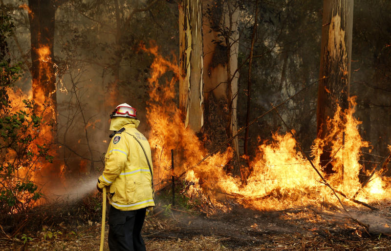 Pictured is a Tuncurry firefighter extinguishing part of the Hillville bushfire south of Taree. Source: AAP