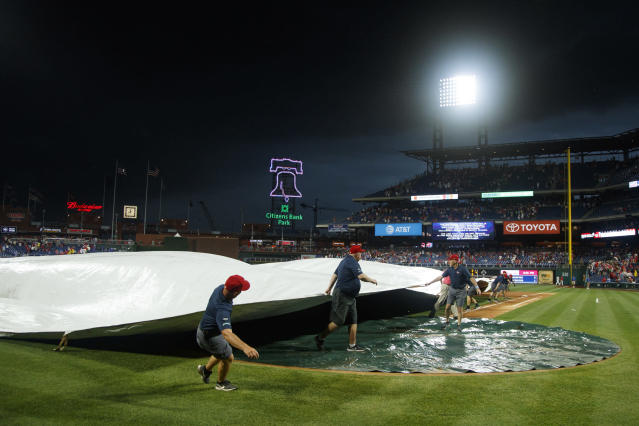 Workers cover the infield as inclement weather delays a baseball game between the Philadelphia Phillies and the Los Angeles Dodgers, Wednesday, July 17, 2019, in Philadelphia. (AP Photo/Matt Slocum)