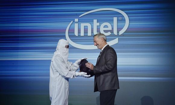 """Outgoing Intel executive Stacy Smith on the right being handed a silicon wafer by an engineer in a """"bunny suit"""" on the left."""