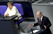 FILE - In this Sept. 29, 2020 file photo, German Finance Minister Olaf Scholz, right, delivers a speech beside German Chancellor Angela Merkel, left, during a budget debate as part of a meeting of the German federal parliament, Bundestag, at the Reichstag building in Berlin, Germany, Tuesday, Sept. 29, 2020. The coronavirus pandemic is colliding with politics as Germany embarks on its vaccination drive and one of the most unpredictable election years in its post-World War II history. (AP Photo/Michael Sohn, File)