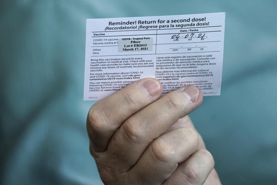 Juan Carlos Guerrero, 62 holds his second shot reminder card as he speaks to a healthcare worker after having received a dose of the Pfizer's COVID-19 vaccine, Wednesday, March 17, 2021, at the Miami-Dade County Tropical Park vaccination site in Miami. (AP Photo/Wilfredo Lee)