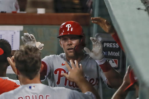 Philadelphia Phillies' Rhys Hoskins is congratulated in the dugout after hitting a solo home run against the Boston Red Sox during the fifth inning of a baseball game Tuesday, Aug. 18, 2020, at Fenway Park in Boston. (AP Photo/Winslow Townson)