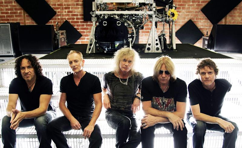 FILE - This May 31, 2012 file photo shows, from left, Vivian Campbell, Phil Collen, Rick Savage, Joe Elliott, and Rick Allen, of musical group Def Leppard in Los Angeles. Kiss and Def Leppard are joining forces for a summer tour. The legendary bands will embark on a U.S. tour June 23 in West Valley City, Utah. (Photo by Matt Sayles/Invision/AP, File)