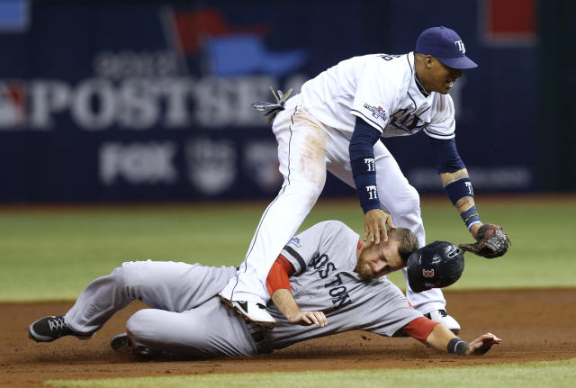 Boston Red Sox's Will Middlebrooks (16) slides under Tampa Bay Rays shortstop Yunel Escobar (11) after he was tagged out on a double play in the third inning in Game 4 of an American League baseball division series, Tuesday, Oct. 8, 2013, in St. Petersburg, Fla. (AP Photo/Mike Carlson)