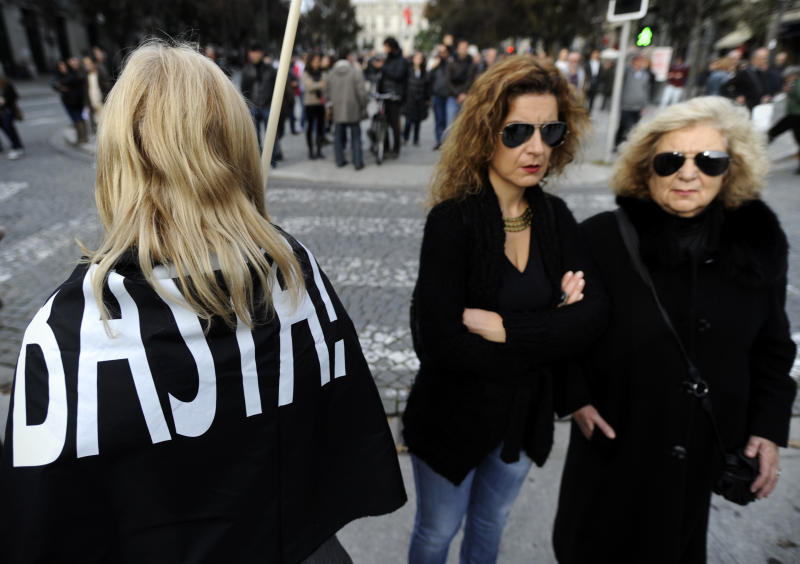 "Women watch as a demonstrator, left, carrying a flag on her shoulders with the words ""Enough!"" prepares to march during a general strike in Porto, Portugal, Wednesday, Nov. 14 2012. The second general strike in eight months in Portugal, where the government intends to intensify austerity measures next year, left commuters stranded as trains ground to a virtual halt and the Lisbon subway shut down. (AP Photo/Paulo Duarte)"
