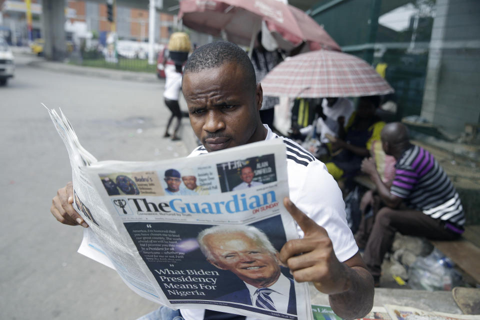 A man reads a newspapers reacting to the news of U.S President-elect Joe Biden's victory in the US presidential election, in Lagos, Nigeria, Sunday, Nov. 8, 2020. (AP Photo/Sunday Alamba)