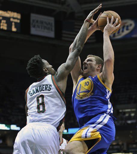 Milwaukee Bucks' Larry Sanders (8) tries to block the shot of Golden State Warriors' David Lee (10) during the first half of an NBA basketball game on Saturday, Jan. 26, 2013, in Milwaukee. (AP Photo/Jim Prisching)