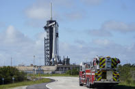NASA firefighters drive on the road outside the fence near a SpaceX Falcon 9 rocket, with the company's Crew Dragon capsule attached, sits on the launch pad at Launch Complex 39A Friday, Nov. 13, 2020, at the Kennedy Space Center in Cape Canaveral, Fla. Four astronauts will fly on the SpaceX Crew-1 mission to the International Space Station scheduled for launch on Nov. 14, 2020 (AP Photo/Chris O'Meara)