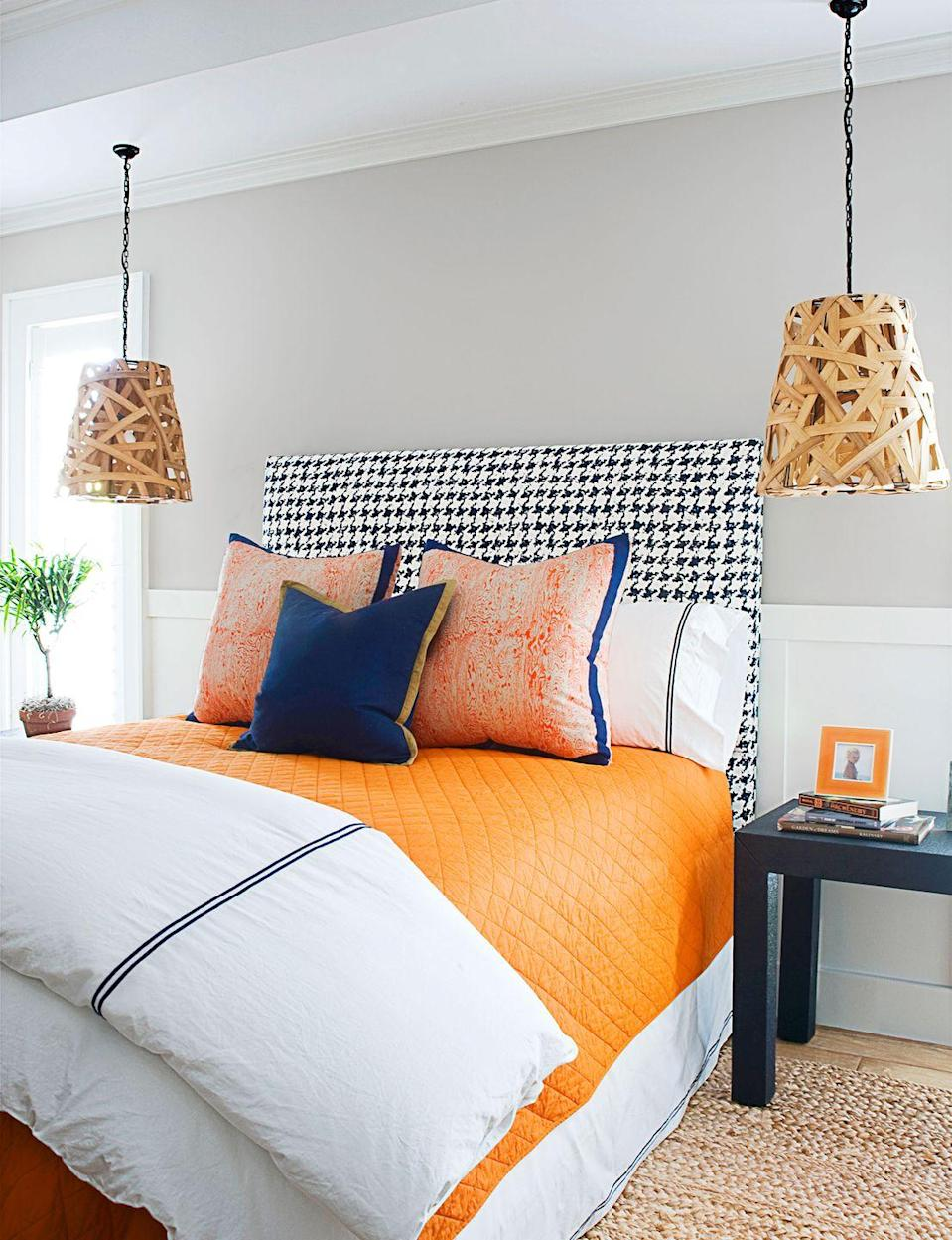 <p>Update the classic blue and white combo with a tangy orange. Dramatic pendant lights also free up storage space on the bedside tables.</p>