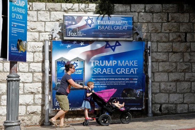 <p>People walk past a banner in support of US President Donald Trump on the day of his visit in Jerusalem on May 22, 2017. (Photo: Menahem Kahana/AFP/Getty Images) </p>
