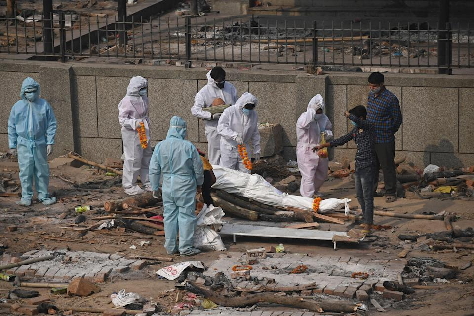 <p>Relatives and friends wearing personal protective equipment (PPE) suits prepare the body of a victim who died due to the Covid-19 coronavirus in New Delhi</p> (AFP via Getty Images)