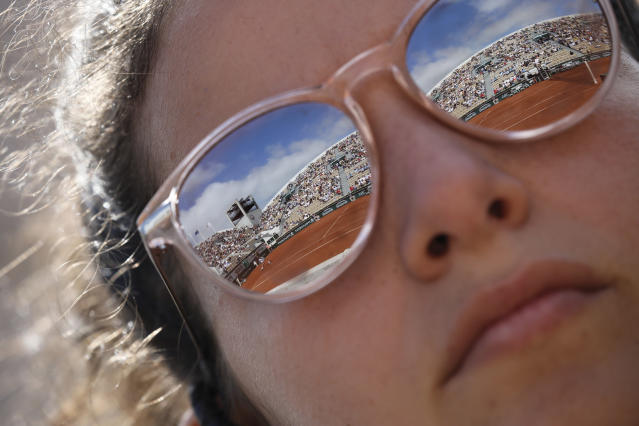Suzanne Lenglen court is reflected in the sunglasses of a women who directs ball girls and boys during the first round matches of the French Open tennis tournament at the Roland Garros stadium in Paris, Sunday, May 26, 2019. (AP Photo/Christophe Ena )