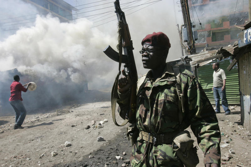 FILE - In this Wednesday, Jan. 2, 2008 file photo, an armed police officer walks past burning buildings during post-election rioting in the Mathare slum of Nairobi, Kenya. The families of seven people shot dead five years ago and eight wounded survivors this week filed a lawsuit to sue the Kenyan government over police brutality in the violence that followed the country's 2007 election, which comes as Kenya prepares for a new election on March 4, 2013 amid warnings from international human rights groups that the police are not ready to prevent electoral violence while refraining from human rights violations. (AP Photo/Karel Prinsloo, File)