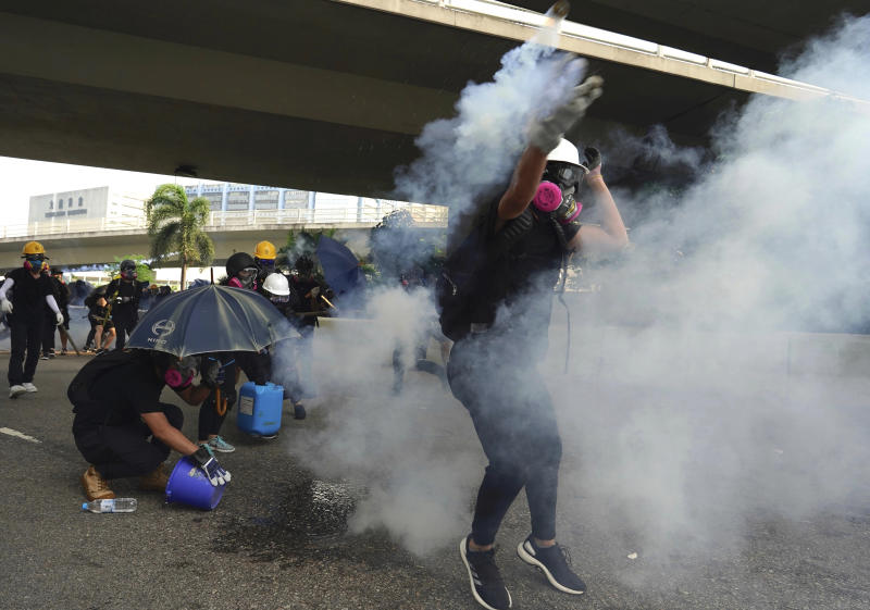 """A demonstrator throws back a tear gas canister during a protest in Hong Kong, Saturday, Aug. 24, 2019. Chinese police said Saturday they released an employee at the British Consulate in Hong Kong as the city's pro-democracy protesters took to the streets again, this time to call for the removal of """"smart lampposts"""" that raised fears of stepped-up surveillance. (AP Photo/Vincent Yu)"""
