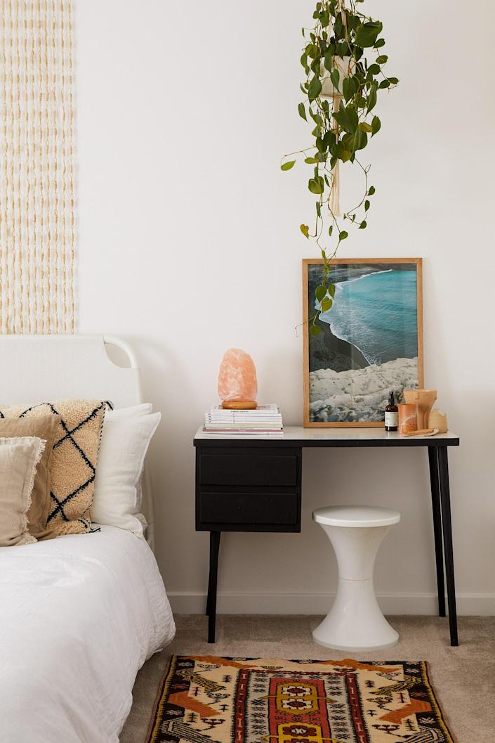 In the guest bedroom, the beaded wall hanging is actually a door curtain the couple brought back from Greece; the desk is a vintage find complemented by a Tam Tam stool from Habitat. Beside the Himalayan salt lamp is a photograph by Ana Kerin of a wild Grecian seascape,bringing character to the room.