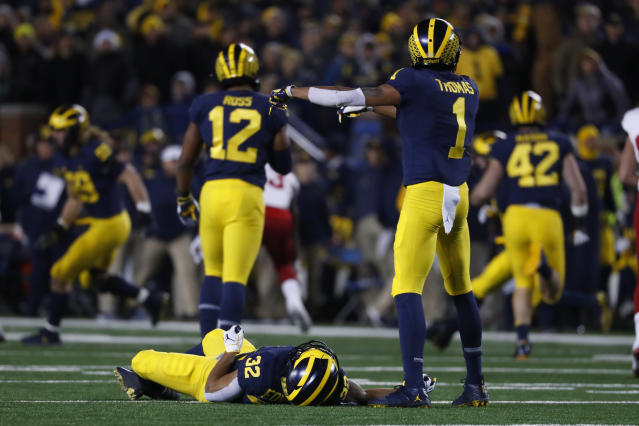 Michigan running back Berkley Edwards (32) lies on the field as Ambry Thomas (1) calls for help after being hit against Indiana during a punt return in the second half of an NCAA college football game in Ann Arbor, Mich., Saturday, Nov. 17, 2018. Indiana linebacker Cam Jones was penalized and ejected for targeting. (AP Photo/Paul Sancya)