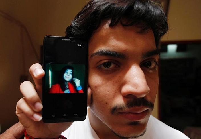Hassan Khan shows the picture of his wife Zeenat Bibi, who was burnt alive by her mother for marrying the man of her choice (AFP Photo/)
