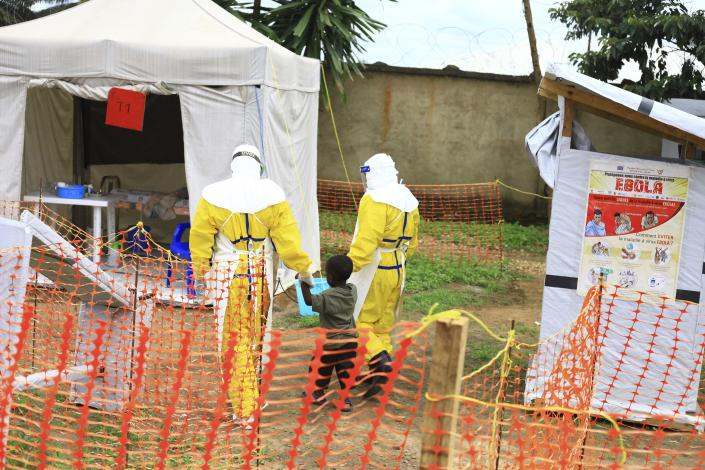 """FILE - In this Sunday, Sept 9, 2018 file photo, health workers walk with a boy suspected of having the Ebola virus at an Ebola treatment centre in Beni, Eastern Congo. The World Health Organization says the risk of the deadly Ebola virus spreading from Congo is now """"very high"""" after two confirmed cases were discovered near the Uganda border. The outbreak in northeastern Congo is larger than the previous one in the northwest and more complicated for health officials with insecurity from rebel groups. As of Friday, Sept. 28 there were 124 confirmed Ebola cases including 71 deaths. (AP Photo/Al-hadji Kudra Maliro, file)"""