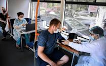A doctor examines a patient inside a trolleybus equipped with a vaccination station in central Chisinau