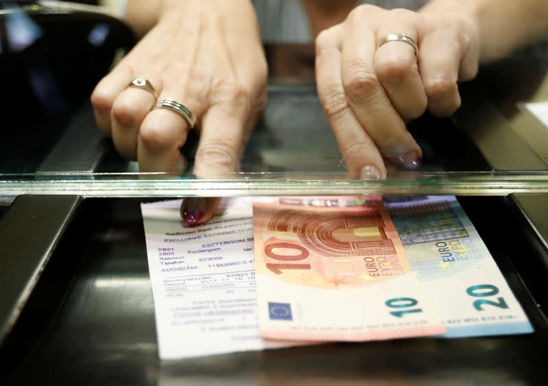 Hungarian woman exchanges forints for euros at a currency exchange shop in Esztergom