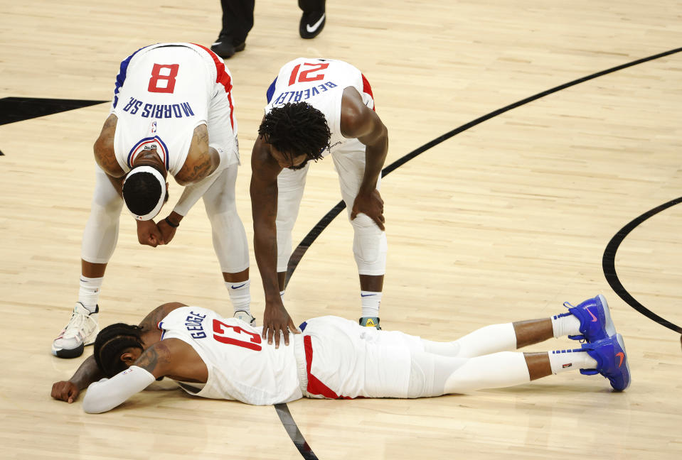 Marcus Morris and Patrick Beverley check on Clippers teammate Paul George after a hard foul in Game 5 of the Western Conference finals. (Christian Petersen/Getty Images)