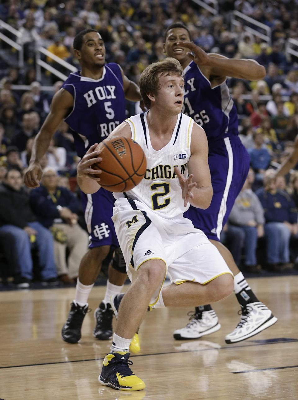Michigan guard Spike Albrecht (2) looks to pass under the basket during the first half of an NCAA college basketball game against Holy Cross in Ann Arbor, Mich., Saturday, Dec. 28, 2013. At rear are Holy Cross' Cullen Hamilton (5) and Malachi Alexander. (AP Photo/Carlos Osorio)