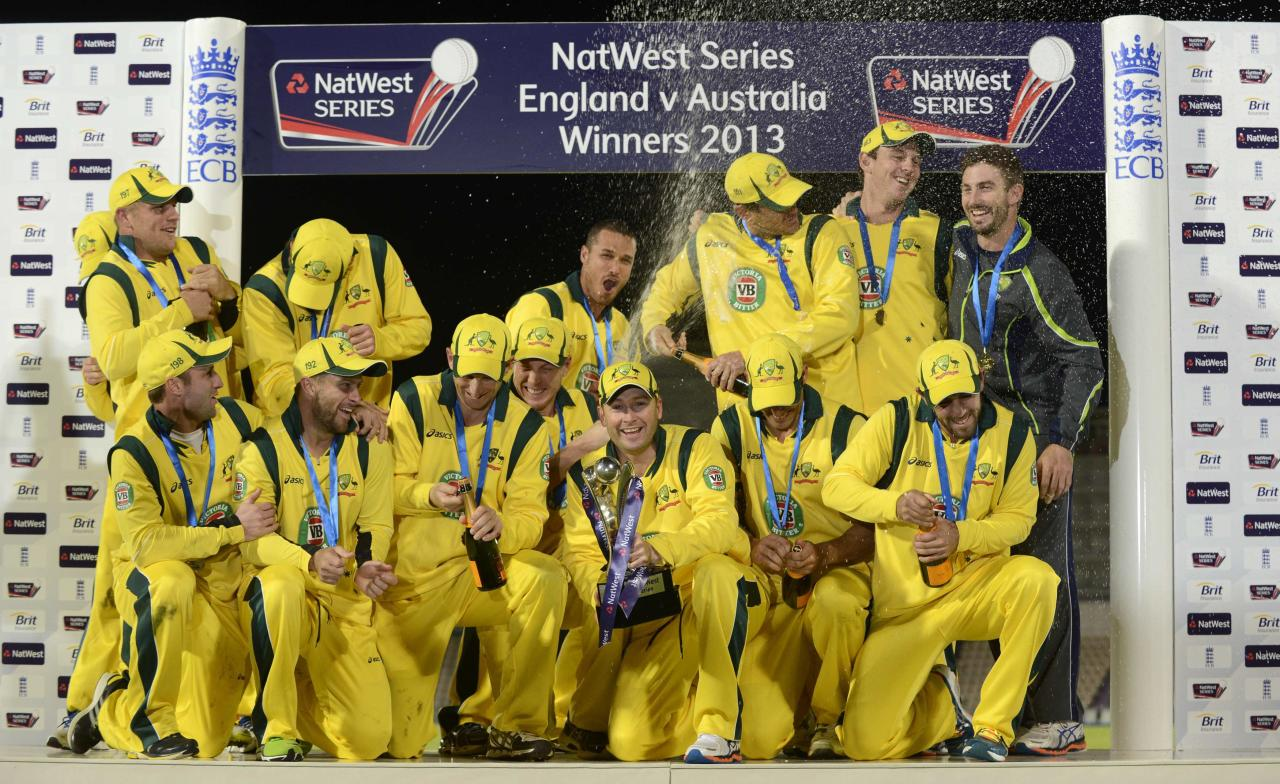 Australia's Michael Clarke (bottom C) holds the trophy after winning the fifth one-day international against England at the Rose Bowl in Southampton, England September 16, 2013. Australia's three most talented players made significant contributions to take their team to a 49-run victory in the deciding final one-dayer against England on a chilly evening at the Rose Bowl in Southampton on Monday. REUTERS/Philip Brown (BRITAIN - Tags: SPORT CRICKET)