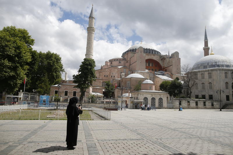 A Womacks takes photos of the Byzantine-era Hagia Sophia, an UNESCO World Heritage site and one of Istanbul's main tourist attractions in the historic Sultanahmet district of Istanbul, Friday, July 10, 2020.  Turkey's Council of State, the country's highest administrative court is expected to release a ruling on a petition requesting that a 1934 decision that turned the Hagia Sophia into a museum be annulled. (AP Photo/Emrah Gurel)