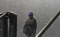 A Chicago Cubs' security guard stands in a storm during a rain delay in the 10th inning of a baseball game against the New York Mets on Tuesday, Aug. 28, 2018, in Chicago. (AP Photo/Matt Marton)