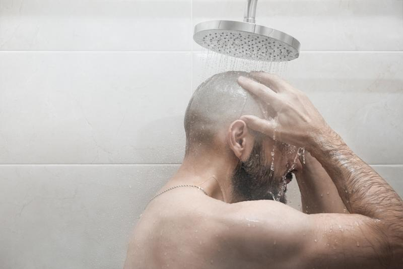 A man washes in the shower. Side view