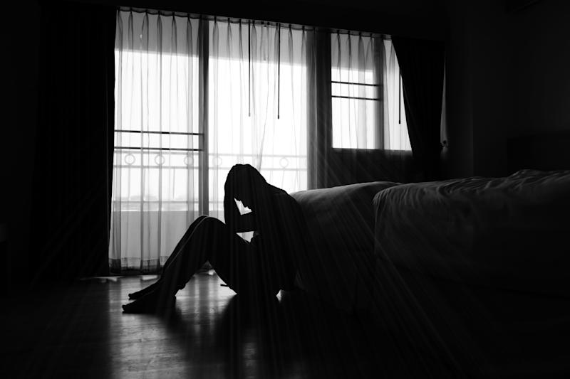 Silhouette of depressed man sitting in the private room