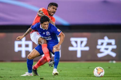 Paulinho (top) of Guangzhou Evergrande fights for the ball with Alexander N'Doumbou