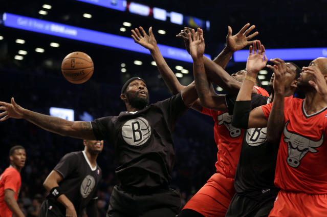 Brooklyn Nets' Reggie Evans, left, fights for a rebound during the first half of the NBA basketball game against the Chicago Bulls at the Barclays Center Wednesday, Dec. 25, 2013, in New York. (AP Photo/Seth Wenig)