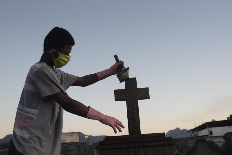 Young man working in a cemetery in Rio de Janeiro, Brazil, on July 5, 2020 painting crosses and cleaning tombs, with a high risk of becoming infected with Corona virus, Covid19, Brazil reaches 135 thousand deaths by covid-19. World life expectancy should fall due to pandemic (Photo by Fabio Teixeira/NurPhoto via Getty Images)