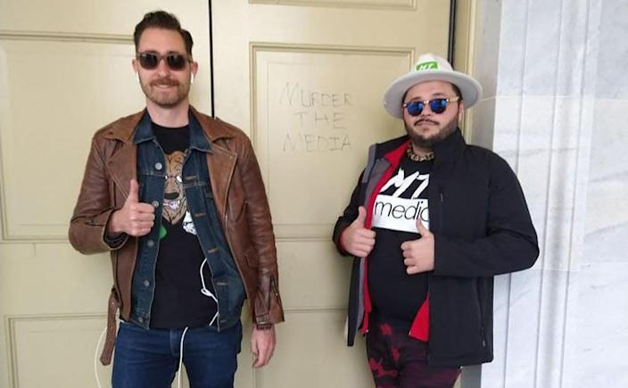 During the siege of the Capitol last Wednesday, Nick Ochs, left, and Dick NeCarlo, right, of the right-wing online streaming outlet Murder The Media pose in front of a message someone scrawled on a door. The pair insist they were covering the riot as independent reporters.