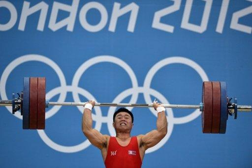 """North Korea's Kim Un-Guk during the men's 62kg weightlifting event at the London Olympics on July 30. North Korea's past and present rulers are inspiring the country's Olympic athletes, according to Pyongyang's official news agency, which reported a """"tumult of joy"""" at its strong showing in London"""