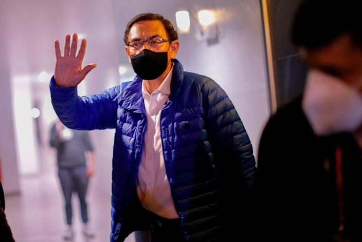 Former Peruvian President Martin Vizcarra waves to the press upon his arrival home after leaving the Presidential Palace in Lima, following his impeachment by an overwhelming majority Congress vote (AFP via Getty Images)
