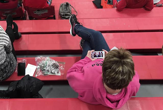 Cathy Pickup watches the State of the Union address on her phone during the Maquoketa High School girls' basketball game. (Photo: Holly Bailey/Yahoo News)