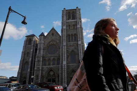 A pedestrian passes the Cathedral of the Holy Cross, where Cardinal Bernard Law, the former Archbishop of Boston who resigned in 2002 in disgrace after covering up years of sexual abuse of children, served in Boston, Massachusetts, U.S., December 20, 2017.   REUTERS/Brian Snyder